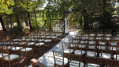 Outdoor ceremony with arch and chairs